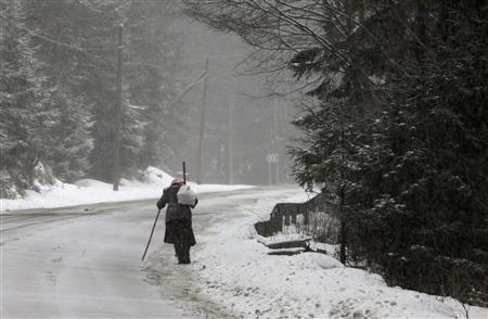 A woman walks uphill on a road during a snowstorm near Prundu Bargaului village, 460 km (282 miles) north of Bucharest, March 2, 2013. REUTERS/Radu Sigheti