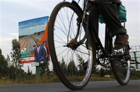 A man cycles past a campaign poster promoting infrastructure by Kenya's Prime Minister and presidential candidate Raila Odinga and his running mate Kalonzo Musyoka in the western town of Kisumu, March 3, 2013. REUTERS/Thomas Mukoya