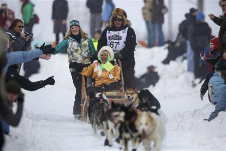 Sonny Lindner's team races down Cordova Street during the ceremonial start to the Iditarod dog sled race in downtown Anchorage, Alaska March 2, 2013. REUTERS/Nathaniel Wilder