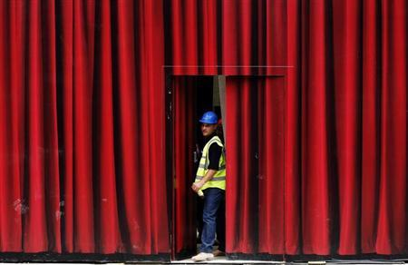 A worker closes a door in a hoarding made to look like a theatre curtain, at a construction site in Covent Garden in London July 2, 2010. REUTERS/Luke MacGregor