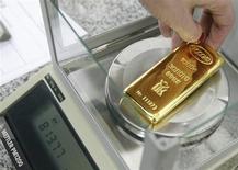 Работник красноярского завода Красцветмет взвешивает слиток золота 25 февраля 2013 года. Цены на золото незначительно растут с недельного минимума при поддержке покупок на физическом рынке Азии, но сильные экономические показатели США снижают привлекательность золота как надежного вложения. REUTERS/Ilya Naymushin