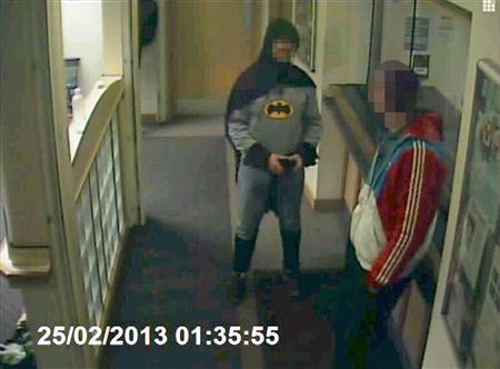 A man dressed as Batman and a burglary suspect stand in a police station in Bradford, northern England, on February 25, 2013, in this still photograph taken from video and provided by West Yorkshire Police on March 4, 2013. A mystery man dressed as Batman demonstrated the same crime-fighting skills as the caped crusader when he handed over a suspect wanted for burglary in Britain. Closed-circuit television footage showed a portly figure wearing an ill-fitting costume including gloves, cape and mask, bringing a 27-year-old man to a police station in Bradford in northern England. REUTERS/West Yorkshire Police/Handout