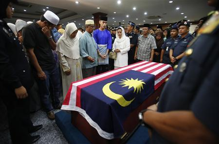 Family members and friends of Malaysian police Superintendent Ibrahim Lebar who was killed on Saturday in Semporna, Sabah, recite prayers near his coffin after its arrival at an airport in Subang, outside Kuala Lumpur March 4, 2013. REUTERS/Bazuki Muhammad