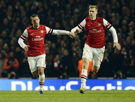 Arsenal's Lukas Podolski (L) celebrates with teammate Per Mertesacker after scoring against Bayern Munich during their Champions League soccer match at the Emirates Stadium in London February 19, 2013. REUTERS/Dylan Martinez