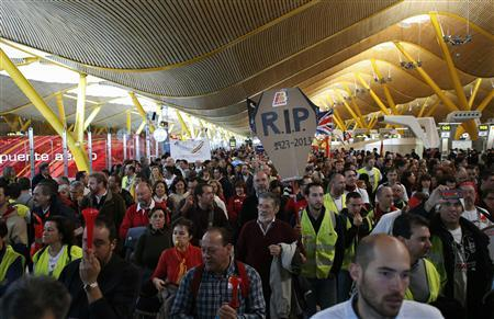 Iberia employees protest in Terminal 4 of Barajas airport during an Iberia strike, the second of three five-day stoppages planned for February and March, in Madrid, March 4, 2013. Workers at Iberia were set to protest at Madrid's Barajas airport at midday on Monday as part of a strike over job and pay cuts at the loss-making airline that will ground nearly 1,300 flights this week. Iberia is part of International Airlines Group, which also includes British Airways and which last week pledged to press ahead with plans to slash 3,800 jobs at the struggling Spanish airline, or 19 percent of the total, despite union opposition. REUTERS/Juan Medina (SPAIN - Tags: TRANSPORT CIVIL UNREST POLITICS BUSINESS EMPLOYMENT)