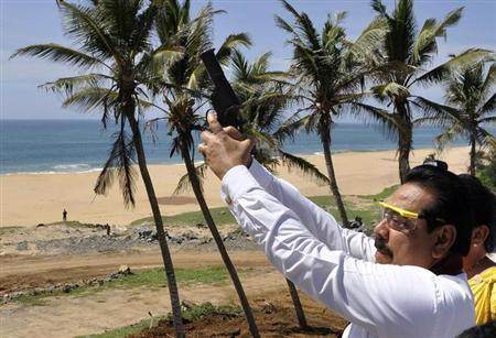 Sri Lanka's President Mahinda Rajapaksa prepares to fire a flare to signal the arrival of the first ship docking at the new Mahinda Rajapaksa Port in Hambantota, about 240km (149 miles) south of Colombo, November 18, 2010. REUTERS/Stringer/Files