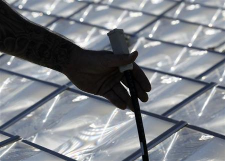 Workers assemble a Pyron Solar 90kWp DC CPV generating system that uses water to stay cool and track the sun in San Diego, California February 9, 2011. REUTERS/Mike Blake