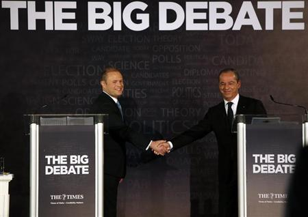 Labour Party and Opposition leader Joseph Muscat (L) and Prime Minister and Nationalist Party leader Lawrence Gonzi shake hands at the end of a political leaders debate organised by The Times newspaper at the Intercontinental Hotel in St Julian's, outside Valletta, February 26, 2013. REUTERS/Darrin Zammit Lupi