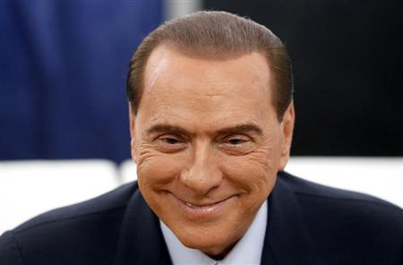 Former Prime Minister Silvio Berlusconi smiles before casting his vote at the polling station in Milan, February 24, 2013. REUTERS/Stefano Rellandini