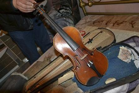 A Bulgarian police official shows a violin, which the Interior Ministry says carries the sign of Antonio Stradivarius, in this handout photo released on February 28, 2013. REUTERS/Bulgarian Interior Ministry Press Office/Handout