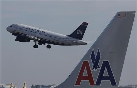 A US Airways jet departs Washington's Reagan National Airport next to an American Airlines jet outside Washington, February 25, 2013. REUTERS/Larry Downing