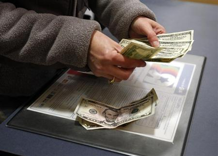 A customer counts her money at the register of a Toys R Us store on the Thanksgiving Day holiday in Manchester, New Hampshire November 22, 2012. REUTERS/Jessica Rinaldi/Files