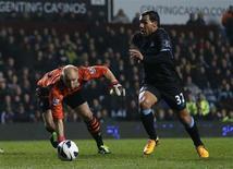 Carlos Tevez passa pelo goleiro Brad Guzan, do Aston Villa, para marcar gol do City nesta segunda-feira. REUTERS/Eddie Keogh
