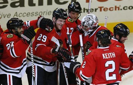 Chicago Blackhawks' goalie Ray Emery (3rd R) is surrounded by teammates after his team's win over the Vancouver Canucks in their NHL hockey game in Chicago, Illinois, February 19, 2013. REUTERS/Jim Young