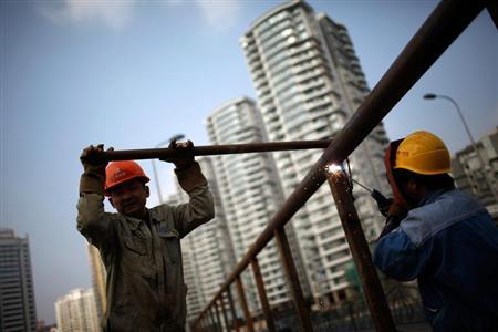 Construction workers work on a bridge in front of a residential site in Shanghai November 20, 2011. REUTERS/Aly Song