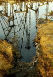 Нефтяные вышки отражаются в луже нефти на месторождении в Баку 16 октября 2005 года. Цены на нефть растут благодаря обещанию Китая поддержать рост экономики на уровне 7,5 процента. REUTERS/David Mdzinarishvili