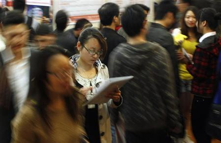 A job seeker looks at her resume during a job fair at a convention center in Shanghai April 7, 2012. REUTERS/Carlos Barria