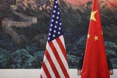 Мужчина готовит флаги США и Китая перед пресс-конференцией в Пекине, 5 сентября 2012 года. США и Китай достигли предварительного соглашения по проекту резолюции о санкциях Совета безопасности, которые накажут Северную Корею за проведенные ею в феврале третьи ядерные испытания. REUTERS/Feng Li/Pool