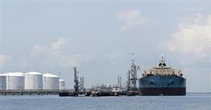 """Сингапурский нефтяной танкер """"Maersk Phoenix"""" стоят на якоре у нефтяного комплекса в порту Пулау-Себарок в Сингапуре 18 апреля 2012 года. Цены на нефть растут во вторник благодаря обещанию Китая поддержать рост экономики на уровне 7,5 процента. REUTERS/Tim Chong"""