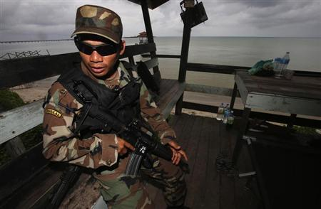 A member of the Royal Malaysian Navy's Naval Special Warfare Forces guards the beach near an area where armed men are holding off, in Felda Sahabat plantation farm, outside Lahad Datu on Borneo island February 19, 2013. REUTERS/Bazuki Muhammad