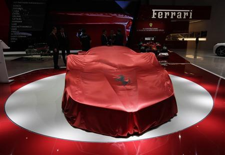 The new Ferrari car is covered on the stand during the first media day of the 83rd Geneva Car Show at the Palexpo Arena in Geneva March 5, 2013. REUTERS/Denis Balibouse