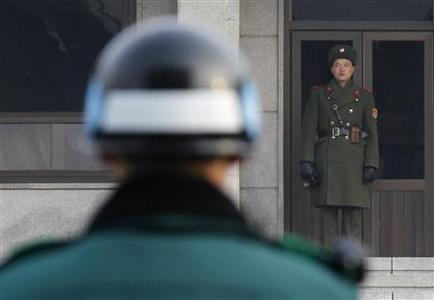 A North Korean (R) and a South Korean soldier face each other at the Panmunjom truce village in the demilitarized zone (DMZ) separating the two Koreas in Paju, about 50 km north of Seoul, December 28, 2011. REUTERS/Kim Kyung-Hoon