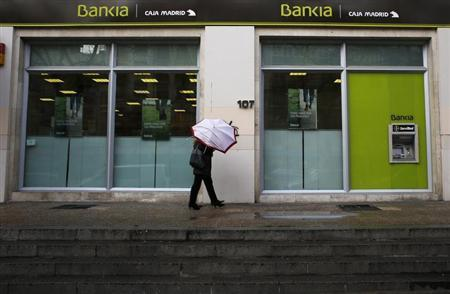 A couple walks with a broken umbrella past a branch of Spain's nationalized lender Bankia in Madrid February 28, 2013. REUTERS/Susana Vera