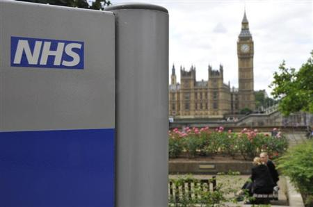A National Health Service (NHS) sign is seen in the grounds of St Thomas' Hospital, in front of the Houses of Parliament in London June 7, 2011. REUTERS/Toby Melville