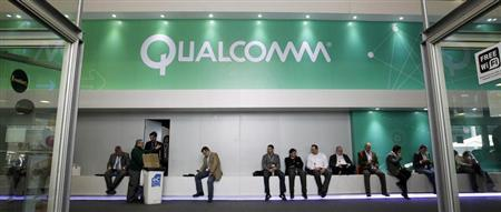 People sit next a Qualcomm stand at the Mobile World Congress at Barcelona, February 27, 2013. REUTERS/Albert Gea