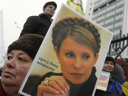 A supporter of jailed opposition leader Yulia Tymoshenko holds a portrait of her during a rally in front of the Appeal Court building in Kiev February 15, 2013. REUTERS/Sergii Polezhaka