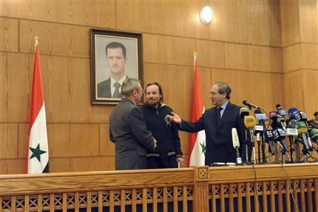 Syria's Deputy Foreign Minister Faisal al-Makdad (R) hands over German journalist Billy Six (C) to Azamat Kulmuhametov, the Russian ambassador to Syria, during a news conference in Damascus March 5, 2013, in this handout photograph released by Syria's national news agency SANA. REUTERS/SANA