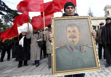 People carry red flags and a portrait of the late Soviet leader Josef Stalin during a ceremony to mark the 60th anniversary of his death in his hometown of Gori, about 80 km (50 miles) west of Georgia's capital Tbilisi March 5, 2013. REUTERS/David Mdzinarishvili