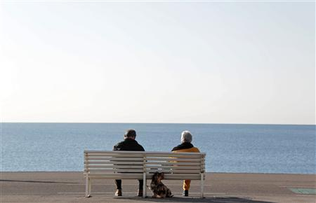 Elderly people sit on a bench to take in the sun with their dog along the Promenade Des Anglais in Nice February 19, 2013. France's President will ask more of old people to fix the hole in the nations retirement coffers but tread gently in doing so. Even a softly-softly approach will mark the first time a left-wing president has dared to tamper with a system which is one of the sacred cows of France's model of generous welfare provision. A plan in the works will likely leave intact the official retirement age of 62 but trim annual pension rises, buying Hollande time to try and coax people in their 50s and 60s to work a few more years, officials working on the project say. Picture taken February 19, 2013 REUTERS/Eric Gaillard (FRANCE - Tags: SOCIETY POLITICS ANIMALS)
