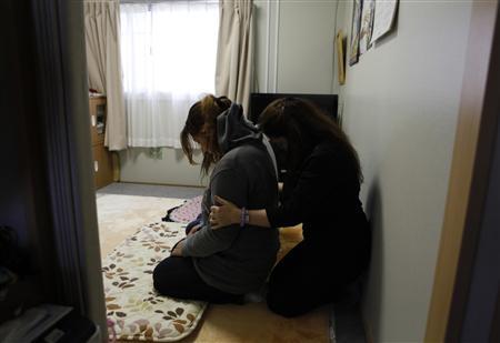 Пятьдесят шесть-летний экзорцист Kansho Aizawa (R) имеет место духовного ритуала очищения для женщин во временном доме в Higashimatsushima, префектура Мияги, 21 февраля 2013 года, накануне второго-летний юбилей 11 марта 2011 землетрясения и цунами.  REUTERS / Chris Meyers