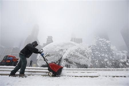 A worker uses a snow blower to clean the steps in front of the Cloud Gate Sculpture, also know as ''The Bean'' during snow in Chicago March 5, 2013. REUTERS/Jim Young