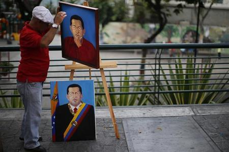 Painter Felix Rodriguez prepares paintings depicting Venezuelan President Hugo Chavez for sale in Caracas March 5, 2013. REUTERS/Jorge Silva