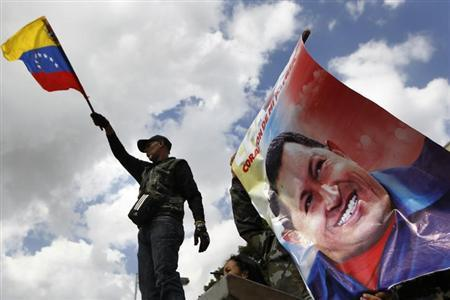 A supporter of Venezuela's President Hugo Chavez waves a national flag next to a giant picture of Chavez, in front of a military hospital where Chavez is being treated, in Caracas February 19, 2013. REUTERS/Carlos Garcia Rawlins/Files