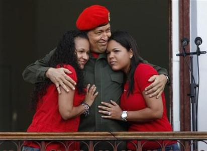 Venezuela's President Hugo Chavez hugs his daughters Rosa (L) and Maria while appearing to supporters on a balcony of Miraflores Palace soon after his return to the country from Cuba, where he underwent surgery and treatment for cancer, in Caracas in this July 4, 2011 file photo. REUTERS/Carlos Garcia Rawlins/Files