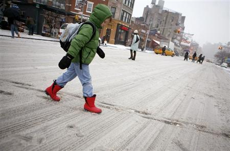 A boy walks crosses a snow covered street on his way to school in New York, February 14, 2007. REUTERS/Eric Thayer