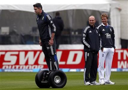 England cricket team player Kevin Pietersen (L) rides a Segway past teammates Jonathan Trott (C) and Nick Compton during a rain delay on the first day of the first test against New Zealand at the University Oval in Dunedin March 6, 2013. REUTERS/David Gray