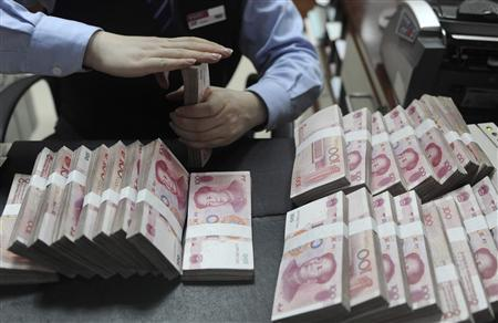 An employee counts Chinese yuan banknotes at a bank in Hefei, Anhui province, in this January 21, 2013 file photo. REUTERS/Stringer/Files