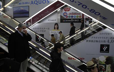 Advertisements for Sharp are seen at a train station in Tokyo March 6, 2013. Samsung Electronics Co is set to invest $110 million in Sharp Corp , ensuring it a stable supply of TV panels and bolstering the survival chances of the Japanese maker of Apple Inc iPhone and iPad screens. REUTERS/Yuya Shino (JAPAN)