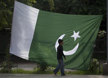 A boy walks past a Pakistani in Rawalpindi August 12, 2012. REUTERS/Faisal Mahmood