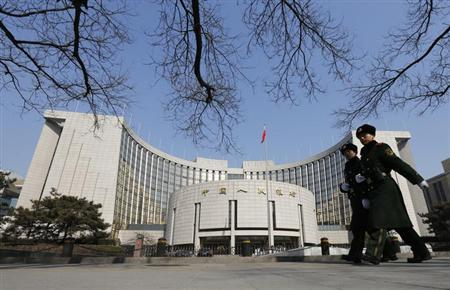 Paramilitary policemen patrol around the headquarters of China's central bank in Beijing February 20, 2013. REUTERS/Kim Kyung-Hoon/Files