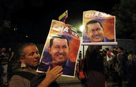 Supporters of Venezuela's President Hugo Chavez show pictures of him as they react to the announcement of his death outside the Venezuelan Embassy in Buenos Aires, March 5, 2013. REUTERS/Marcos Brindicci