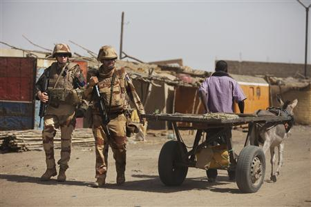 French soldiers pass a donkey-driven cart outside the destroyed main market in Gao, March 2, 2013. REUTERS/Joe Penney