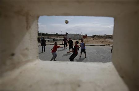 Palestinian children play soccer on a street in Khan Younis in the southern Gaza Strip February 22, 2013. REUTERS/Ibraheem Abu Mustafa