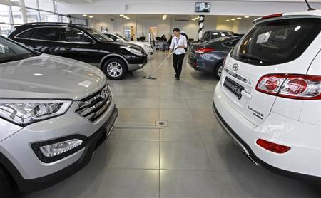 An employee cleans around cars for sale on display in the Hyundai showroom in St.Petersburg January 15, 2013. REUTERS/Alexander Demianchuk
