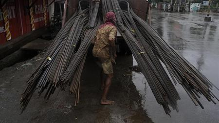 A labourer unloads iron rods from a vehicle as it drizzles at a construction site on the outskirts of Agartala September 26, 2010. REUTERS/Jayanta Dey/Files