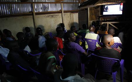 Residents watch the tallying of cast votes on a television set during presidential and parliamentary elections in the western town of Kisumu, 350km (218 miles) from the capital Nairobi, March 5, 2013. REUTERS/Thomas Mukoya